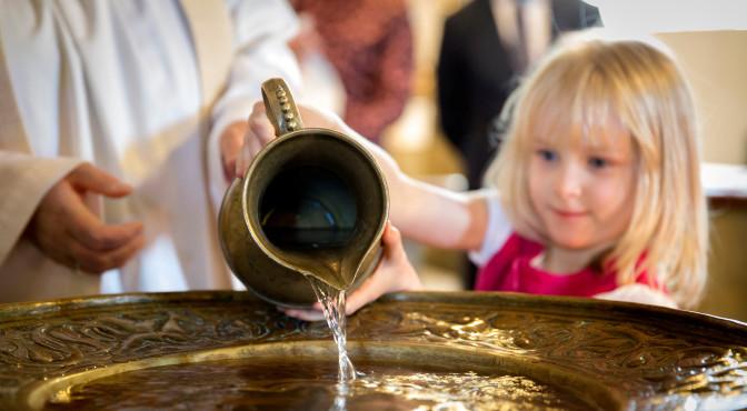 pige hælder vand i dåbsfad